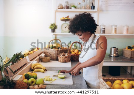 Shot of young african woman working at juice bar and cutting fruits. Female bartender making fresh juice. - stock photo