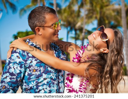 Shot of young beautiful couple enjoying beach getaway. Couple in love, summer luxury vacation in Hawaii. Travel holidays concept. - stock photo