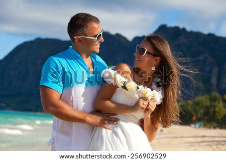 Shot of young couple enjoying beach getaway, looking at each other affectionately. Couple in love, summer luxury vacation in Hawaii. Travel holidays concept. - stock photo