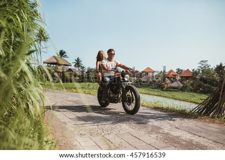 Shot of young couple on motorcycle on rural road. Young man and woman outside riding a motorcycle on a summer day. - stock photo