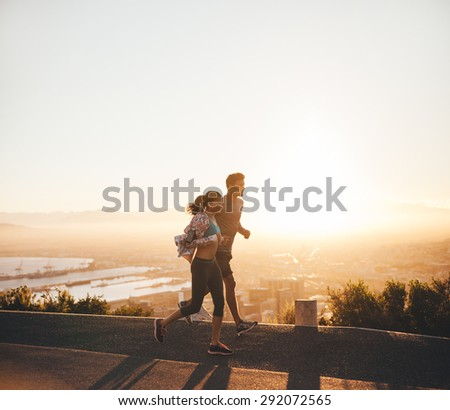 Shot of young couple running together on hillside road. Young man and woman jogging together in early morning. - stock photo