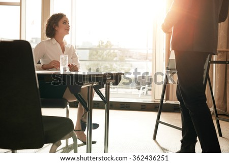 Shot of young female executive sitting at conference table with businessman showing presentation. Businesspeople during business presentation in boardroom.