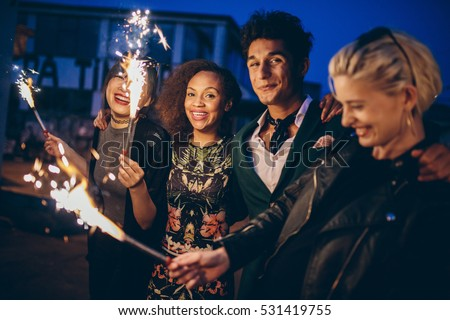 Shot of young friends at night with fireworks enjoying party. Group of friends with sparklers on road in evening.