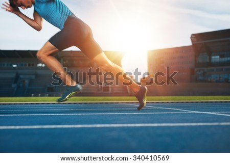 Shot of young male athlete launching off the start line in a race. Runner running on racetrack in athletics stadium.