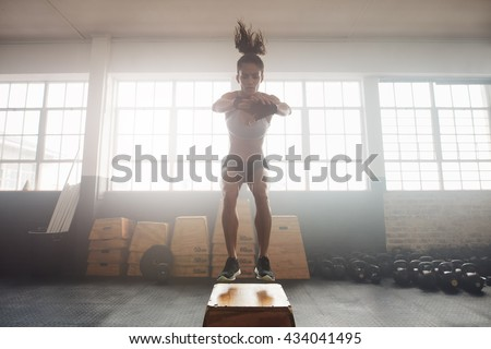 Shot of young woman working out with a box at the gym. Young female athlete box jumping at a crossfit gym. - stock photo