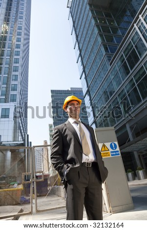 Shot showing a man dressed in a suit and hard hat on a construction site in a modern city environment.