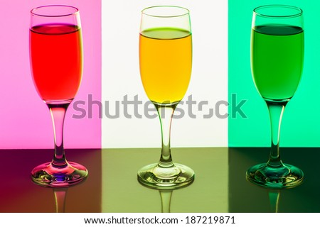 Shot stemware of juice on a symmetrical colored background ... - stock photo