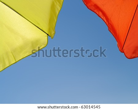 shot taken under a green and orange sun umbrellas against the perfect blue sky - stock photo