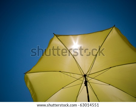 shot taken under a green umbrella against the perfect blue sky - stock photo