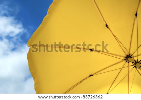 shot taken under a yellow umbrella against the perfect blue sky - stock photo