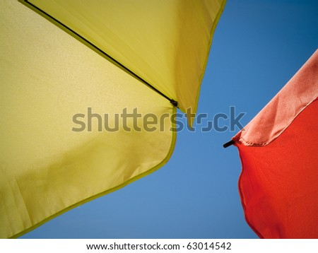 shot taken under green and orange sun umbrellas against the perfect blue sky - stock photo