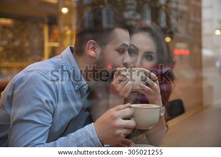 shot through the shopwindow young couple drinking coffee in cafe - stock photo