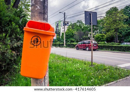 Shot to a dumpster hanged on pillar situated on the side of an empty street - stock photo