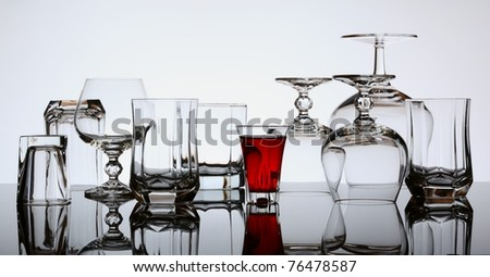 Shot with red alcoholic beverage and many empty glasses - stock photo