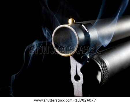 Shotgun barrel that has smoke coming from inside - stock photo