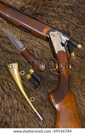 shotgun, cartridges, knife and horn on top of a boar skin - stock photo