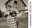 Shotgun Momma protects her moonshining barn with a rather large shotgun. - stock photo
