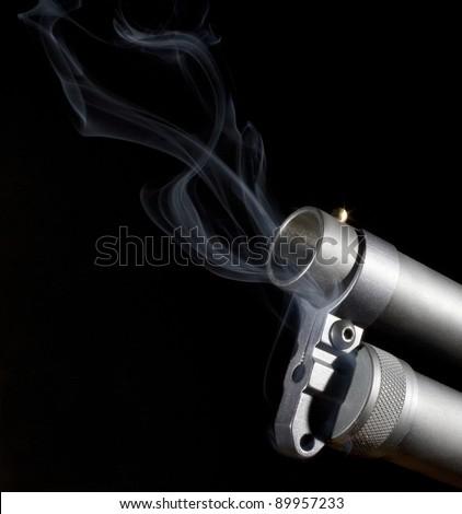 Shotgun that has smoke coming from its barrel and tube magazine - stock photo