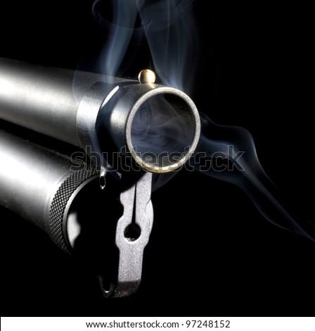 Shotgun that has smoke near and inside of its barrel on black - stock photo
