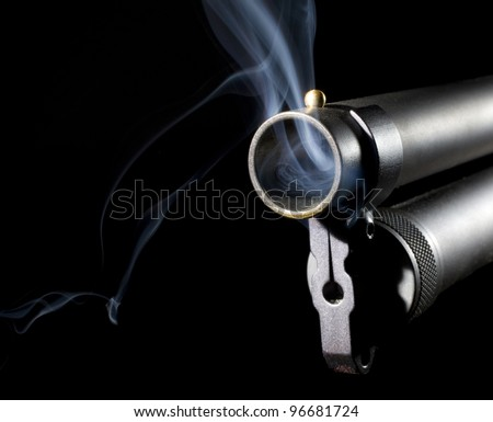 Shotgun that is blowing smoke after is has been used to shoot - stock photo