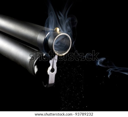 Shotgun that is pouring out smoke as white particles fall - stock photo