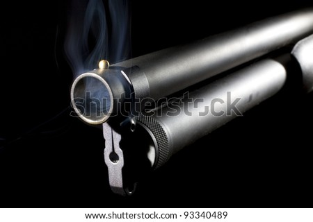 Shotgun that is pump action with smoke coming from its muzzle - stock photo
