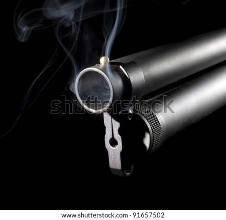 Shotgun with an extended magazine with smoke coming from the muzzle - stock photo