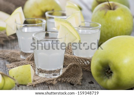 Shots of Apple Liqueur on vintage background - stock photo