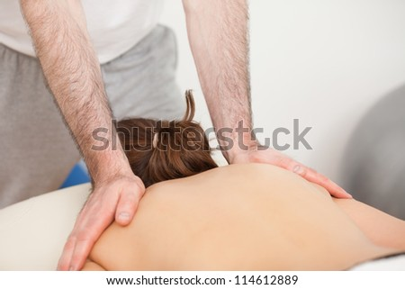 Shoulders of woman being massaged by doctor in a room - stock photo