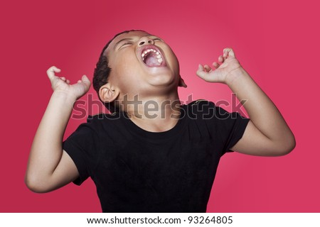 Shouting angry asian kid on red background - stock photo