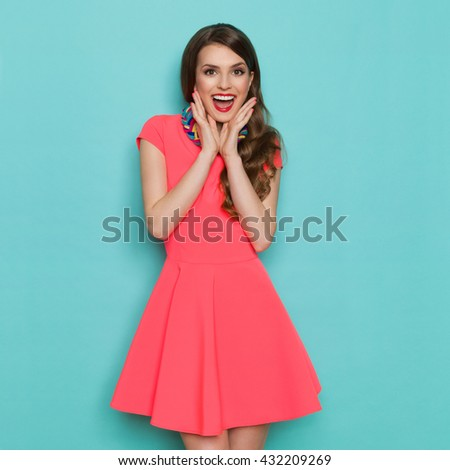 Shouting beautiful young woman in pink mini dress posing with hands on chin. Three quarter length studio shot on turquoise background. - stock photo