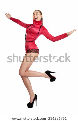 Shouting blond young woman in high heels and pink top standing on one leg. Full length studio shot isolated on white. - stock photo
