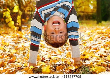 Shouting boy upside down on yellow leaves - stock photo