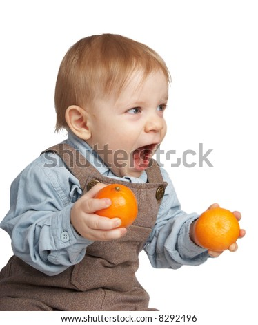 Shouting boy with tangerines in hands