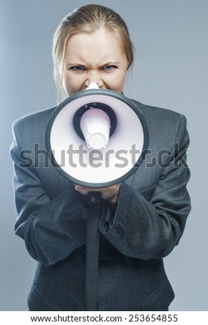 Shouting Caucasian Woman With Big Megaphone. Against Gray Background. Horizontal Composition - stock photo