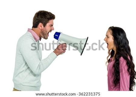 Shouting couple with man holding loudspeaker on white background - stock photo