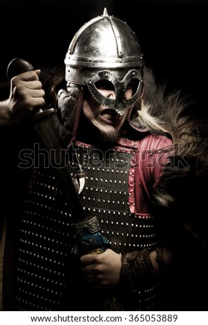 Shouting viking with sword and helmet over black background - stock photo