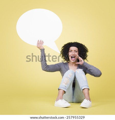 Shouting woman being mad holding a empty white sign board with copy space, isolated on yellow background. - stock photo