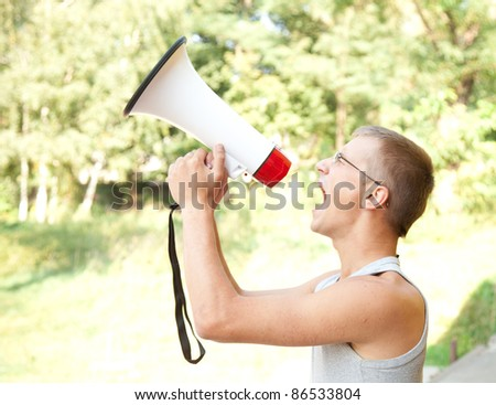 shouting young man in casual shirt with megaphone - stock photo