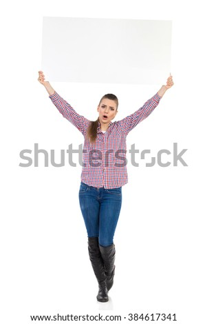 Shouting young woman in jeans, black boots and lumberjack shirt standing and holding banner over her head. Full length studio shot isolated on white.