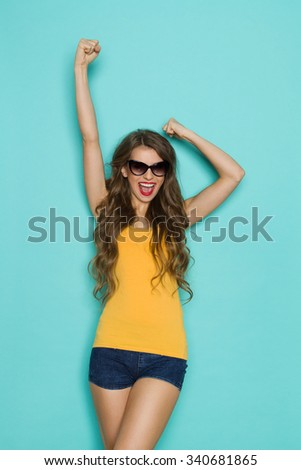 Shouting young woman in jeans shorts and orange shirt posing with arm raised. Three quarter length studio shot on teal background. - stock photo