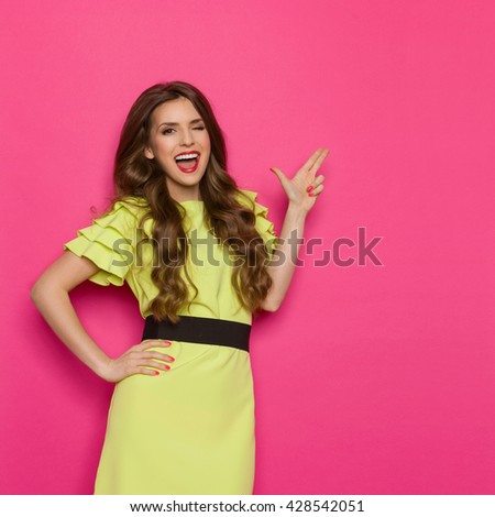 Shouting young woman in lime green dress posing with hand on hip, winking and pointing with finger gun at copy space. Three quarter length studio shot on pink background. - stock photo