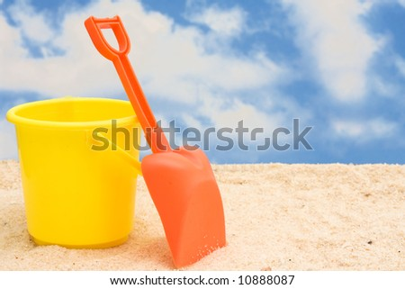 Shovel and bucket in sand – summer time fun - stock photo