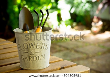 Shovel and gardening fork in bucket on wooden table in garden - vintage style effect picture - stock photo