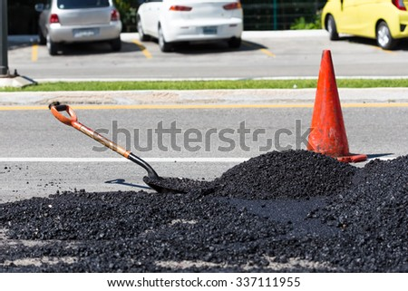 Shovel for road construction works in a heap of new asphalt at street   - stock photo