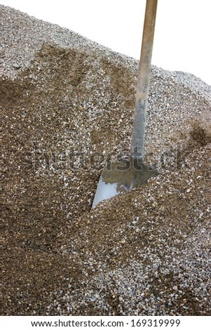 shovel in a heap of gravel at a construction site islolatete on white - stock photo