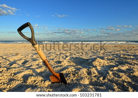 Shovel in Sand at the Beach. Wide angle image of a rusty shovel in the sand on a beach under a partly cloudy blue sky. - stock photo