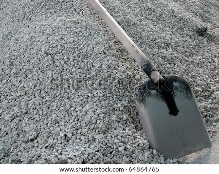 Shovel on a heap of gravel - stock photo