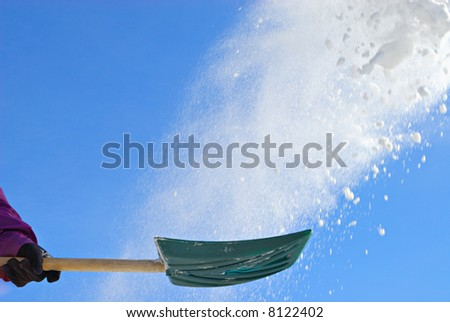 Shovel throwing snow in air - stock photo