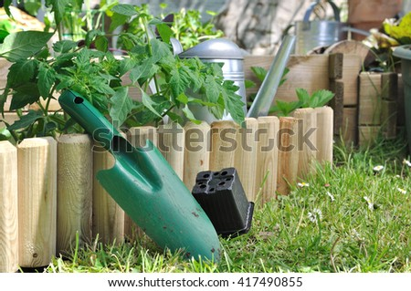 shovel with empty bucket against wooden border of a vegetable patch  - stock photo